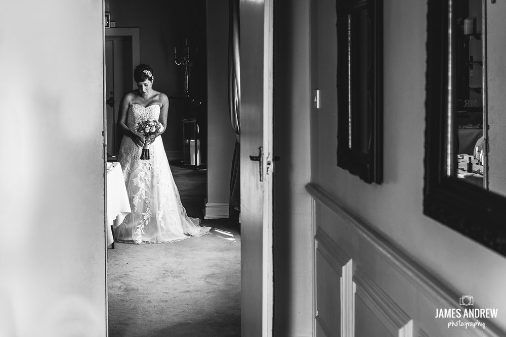 Bide through doorway waiting to walk down the isle