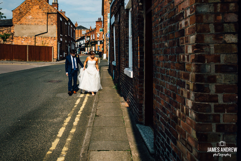 bride and groom walking through back streets urban wedding