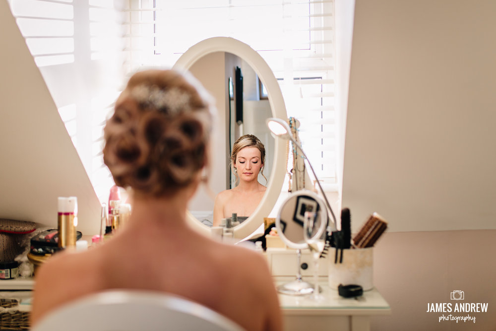 Bride Looking In Mirror getting ready dress