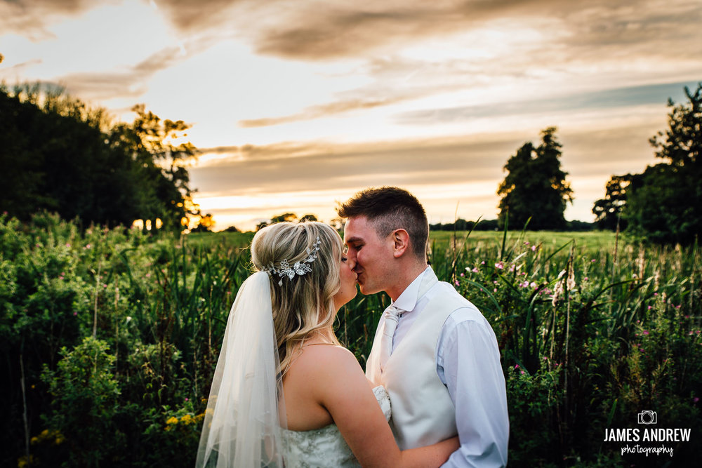 Kissing Couple At Sunset natural relaxed wedding picture