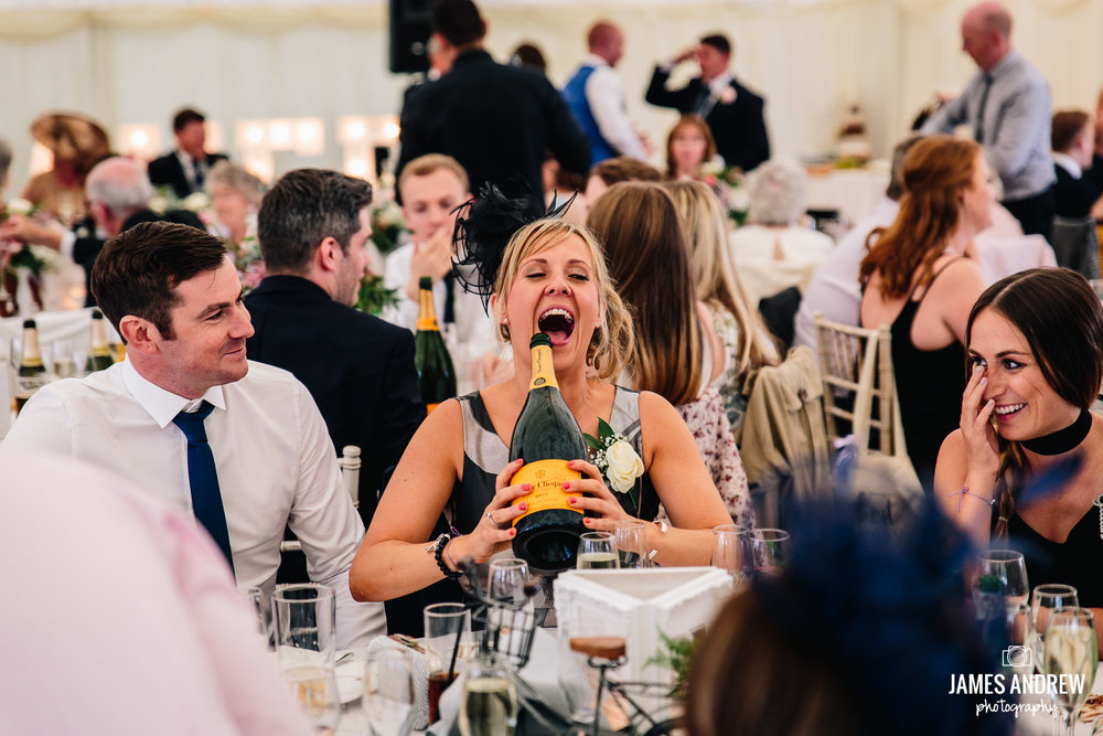 Guest Holding giant Champagne Bottle Laughing out load