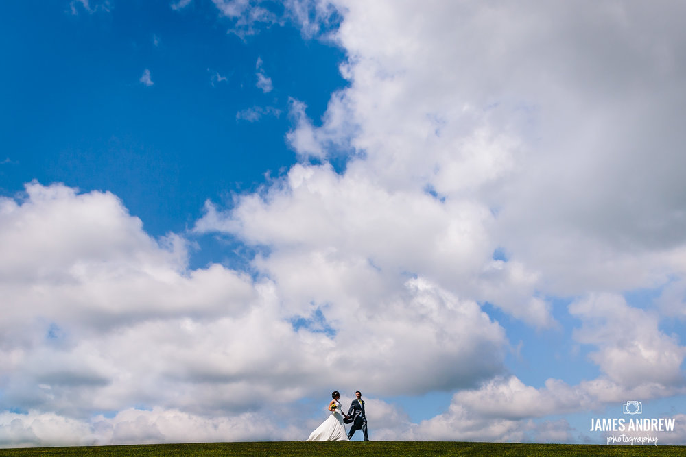 Wedding Couple Walking Under Blue Sky clouds Cheshire