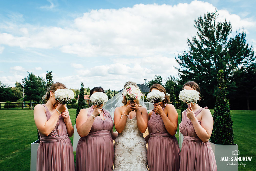 Bridesmaids hide behind flowers