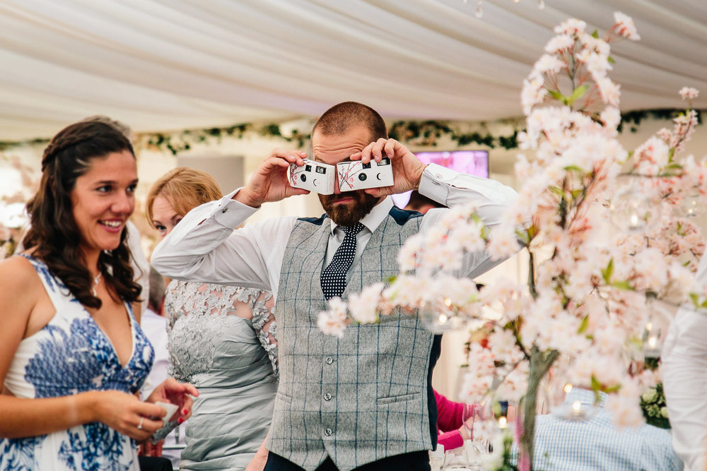 Wedding guest playing round with cameras