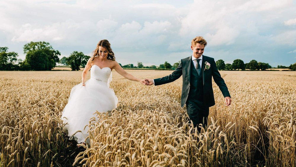 wedding couple walking through field next to Mythe barn in Staffordshire