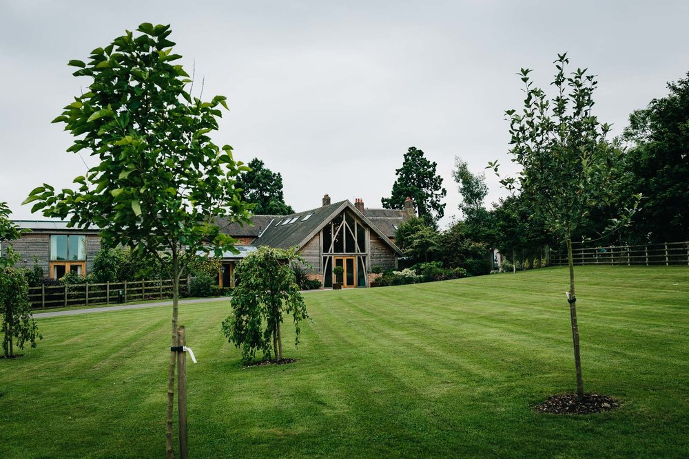 OUTSIDE VIEW LOOKING OVER GREEN GRASS OF MYTHE BARN WEDDING VENUE LEICESTER