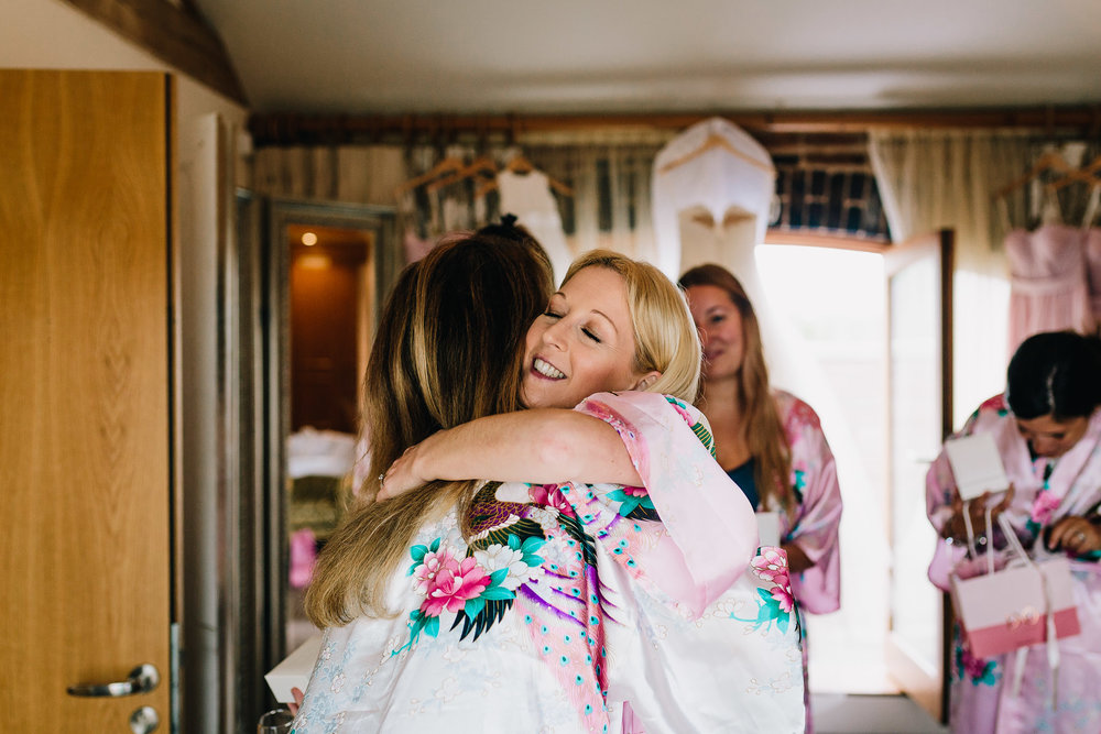 BRIDESMAIDS HUGGING BRIDE ON WEDDING DAY