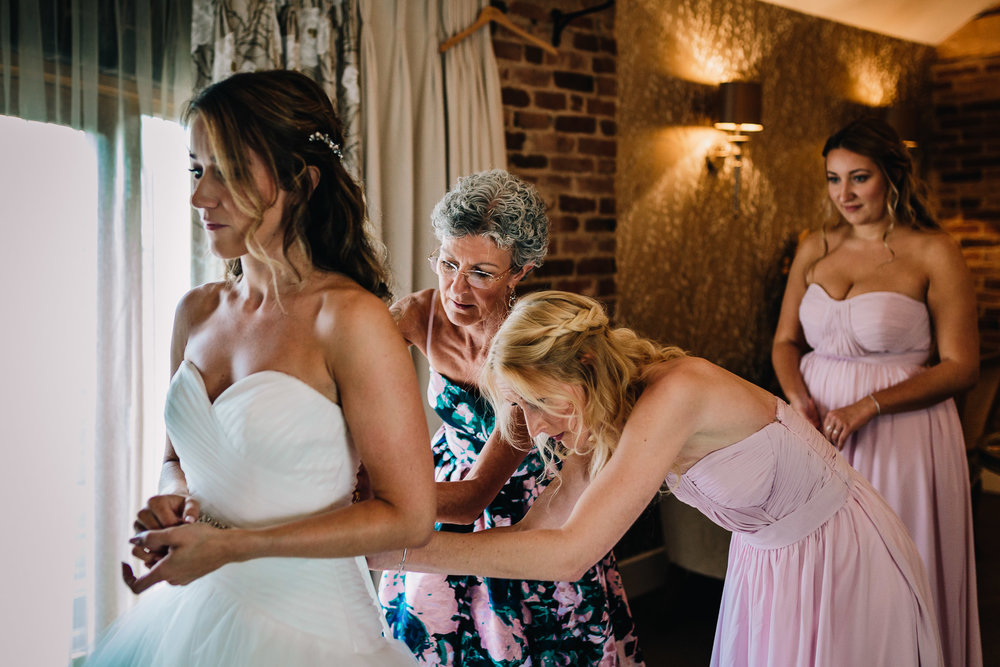 BRIDESMAIDS HELPING BRIDE IN TO WEDDING DRESS