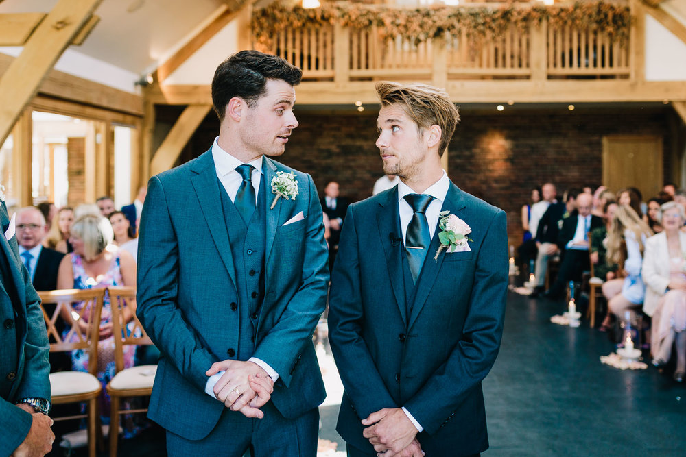 GROOM AND BEST MAN LOOKING AT EACH OTHER NERVOUSLY