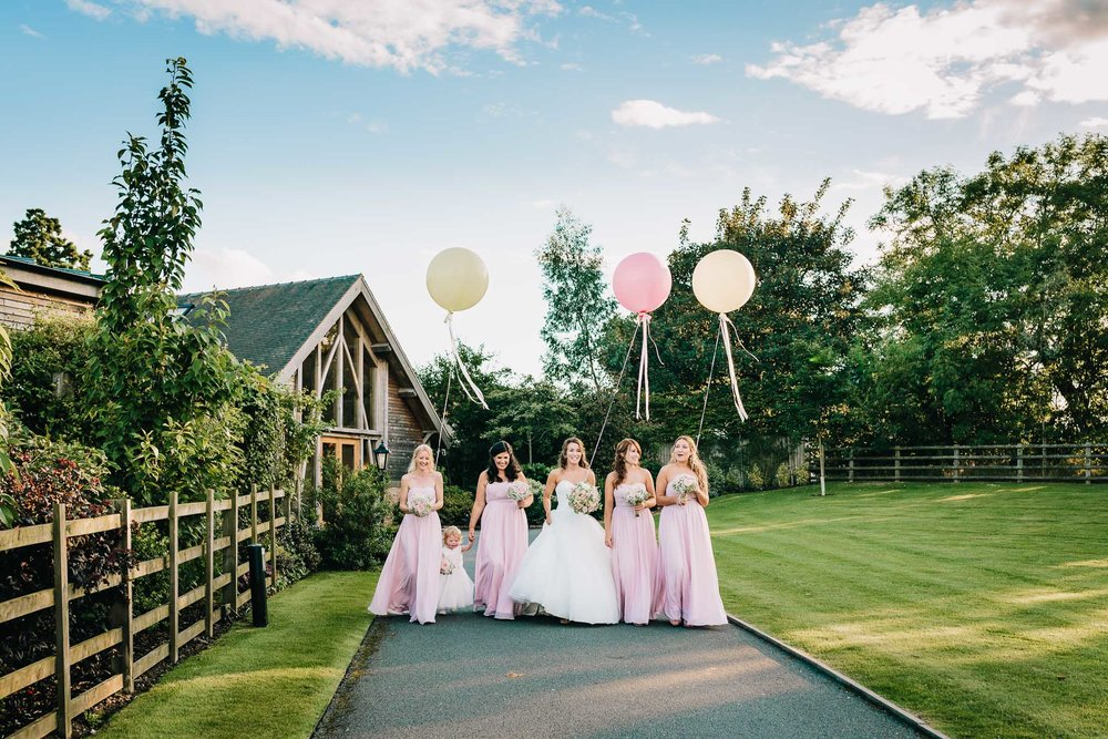 BRIDESMAIDS WALKING TOGTHER WITH PINK WEDDING BALLOONS