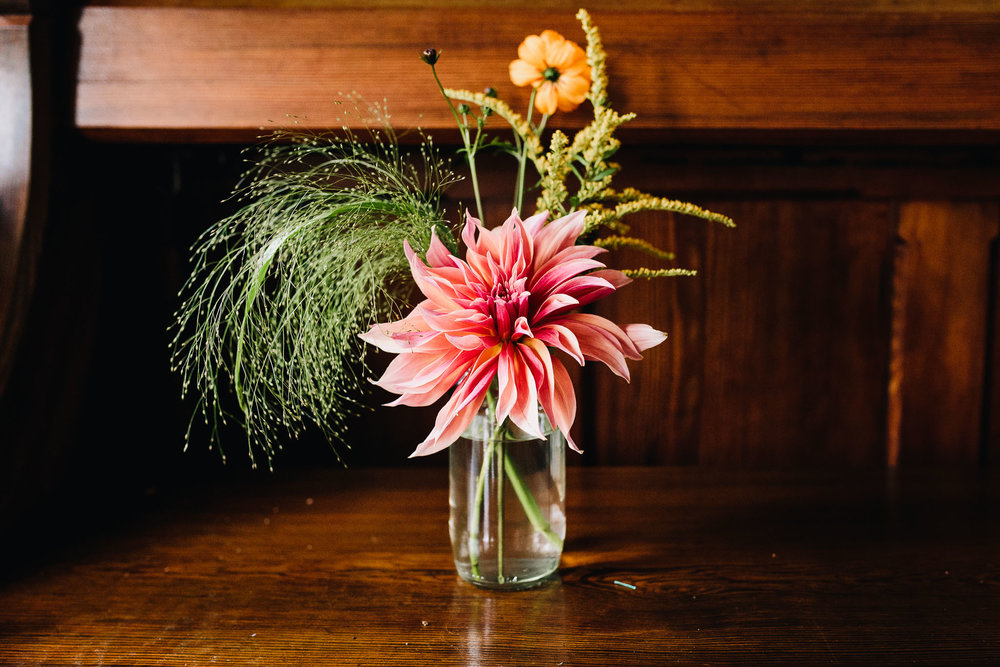 BRIGHTLY COLORED FLOWERS IN JAM JARS IN WELSH BARN