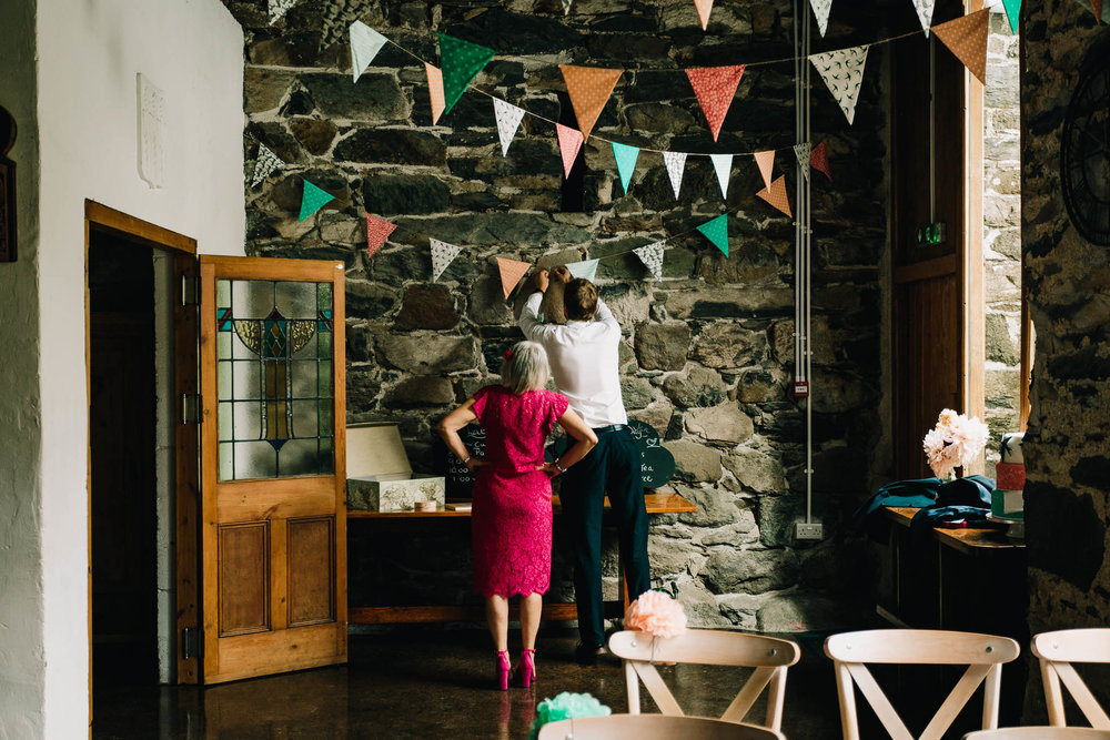 WEDDING GUESTS HELPING TO DECORATE BARN IN WALES