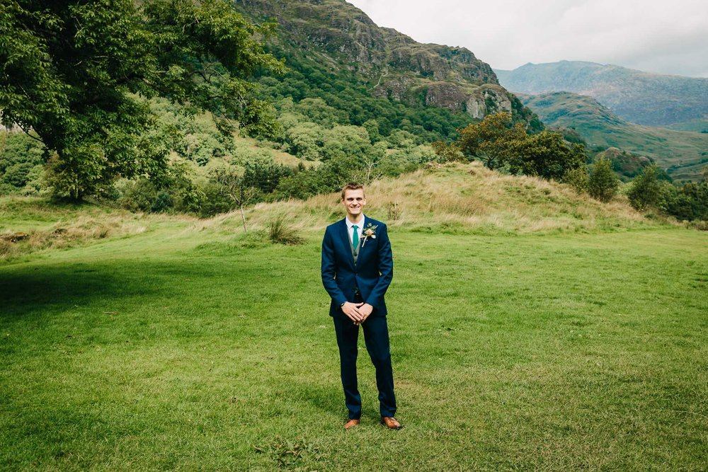 GROOM PORTRAIT BY MOUNTAINS WEARING BLUE SUIT