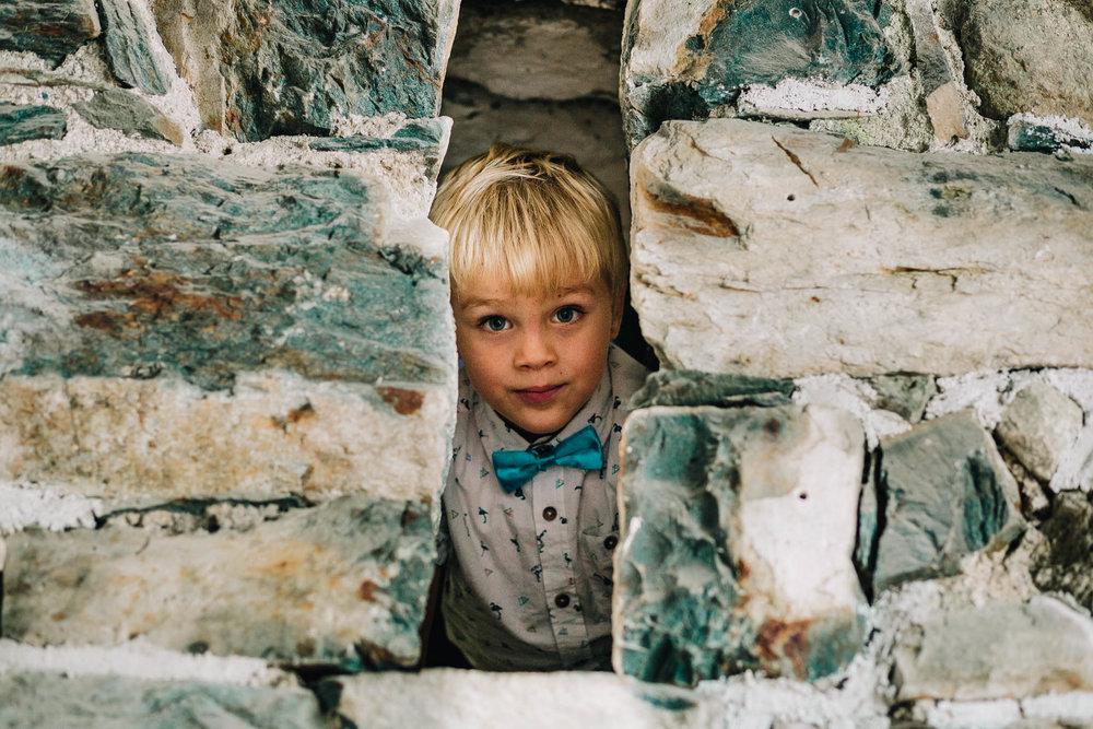 CHEEKY BLONDE BOY PEERING THROUGH GAP IN BARN WALL