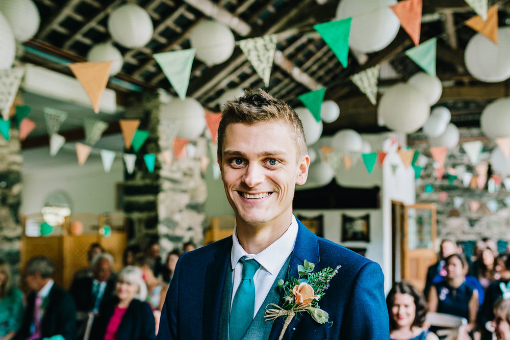 GROOM SMILING WHILE STOOD IN THE ISLE WAITING FOR BRIDE TO ARRIVE