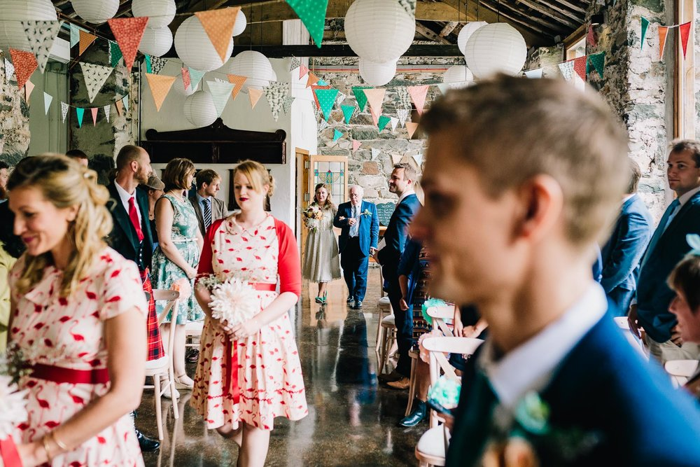 BRIDESMAIDS WEARING WHITE AND RED DRESSES WALKING IN TO WEDDING BARN