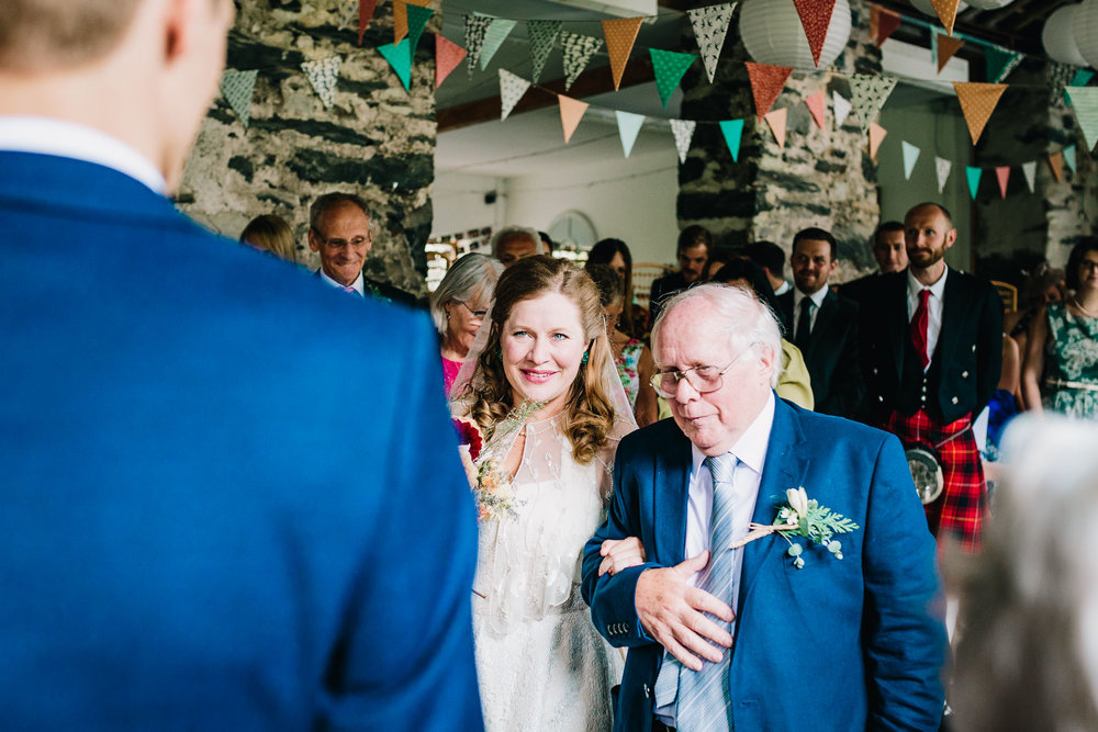 BRIDE AND FATHER WALKING DOWN THE ISLE IN TO STONE BARN WALES