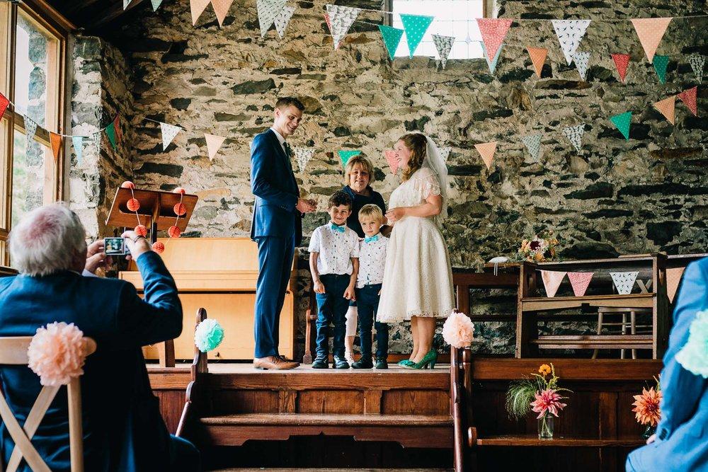 GROOMSMEN PASSING WEDDING RINGS TO COUPLE