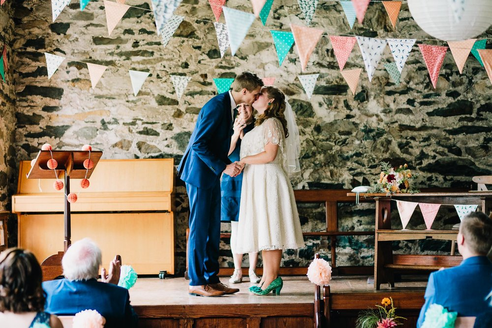 GROOM KISSING HIS BRIDE FOR THE FIRST TIME WITH COLORFUL BUNTING OVERHEAD