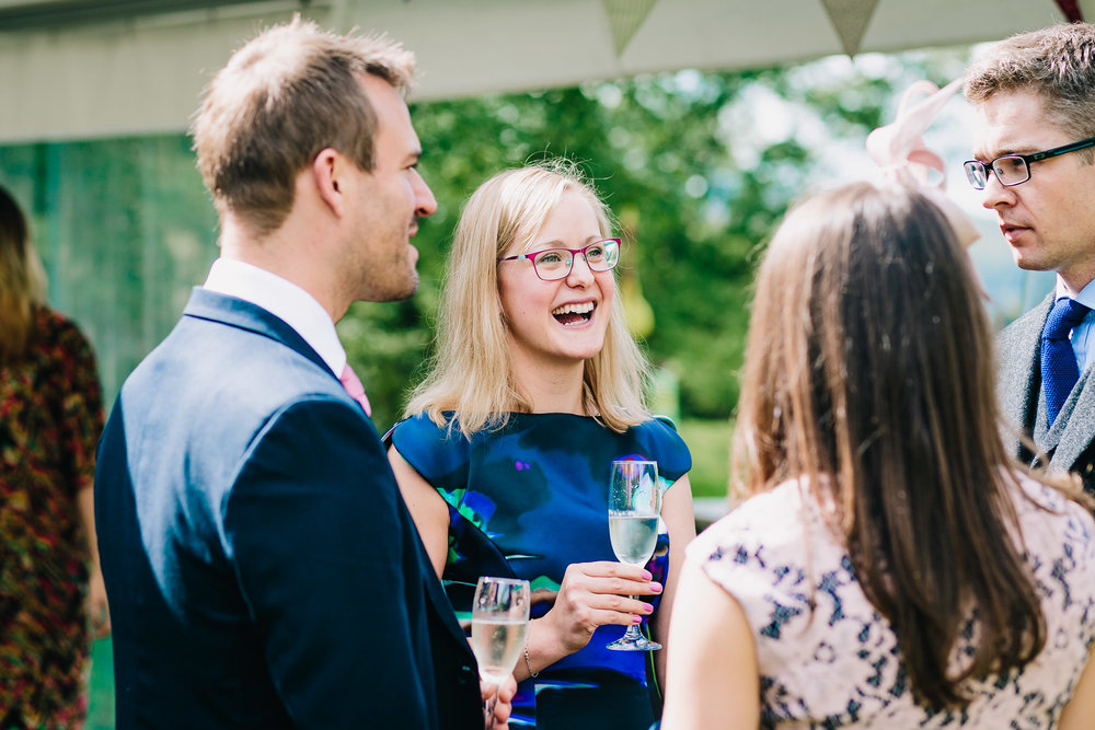 REPORTAGE PICTURE OF FEMALE WEDDING GUEST HAVING FUN AT OUTDOOR WEDDING PARTY