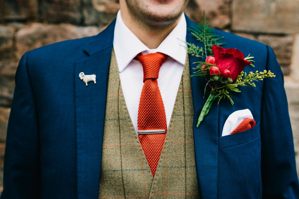 GROOMS SUIT WAISTCOAT ORANGE TIE AND RAM PIN