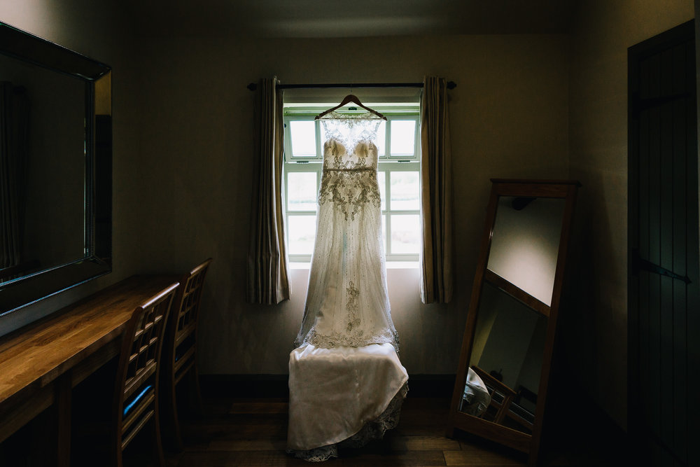 WEDDING DRESS HANGING IN WINDOW