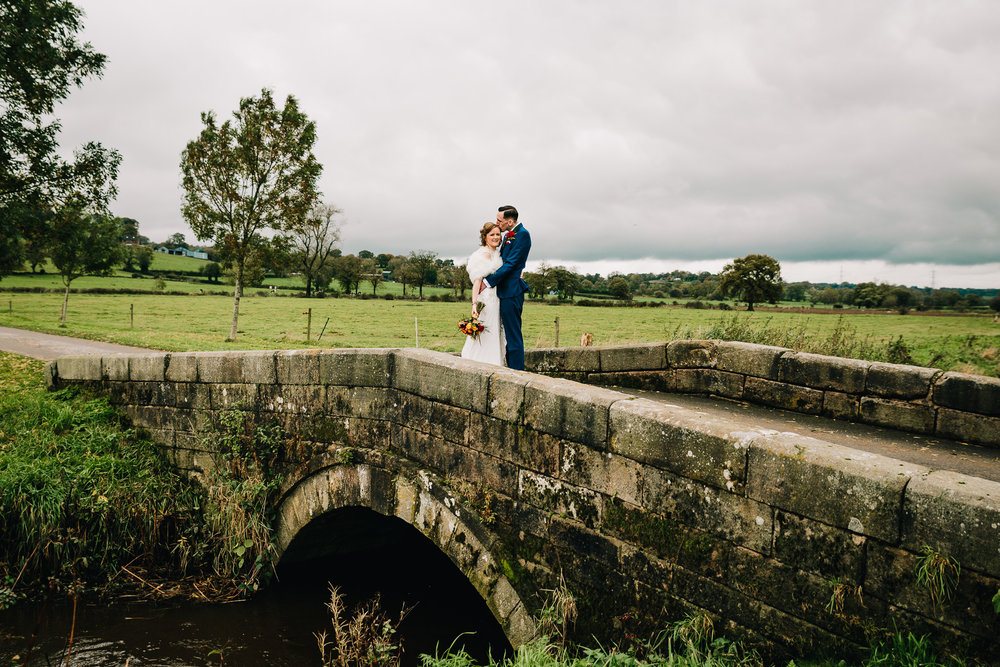 ROMANTIC PORTRAIT OF WEDDING COUPLE ON BRIDGE