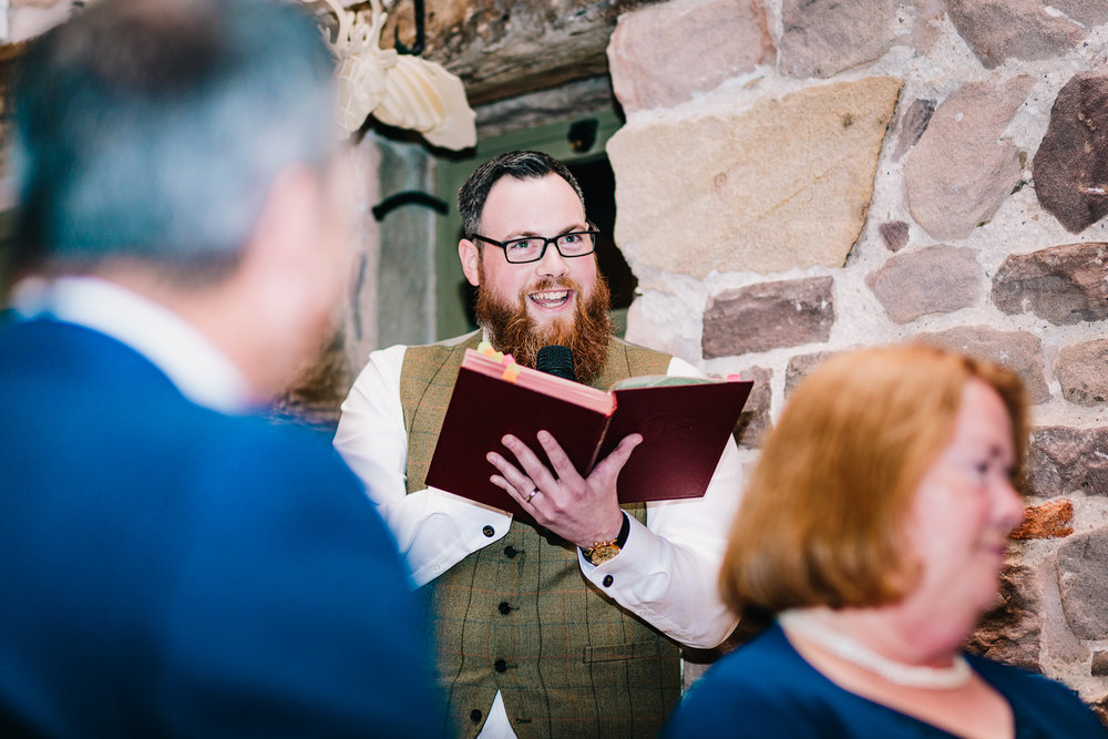 BEST MAN READING FROM GIANT BOOK WHILE DELIVERING SPEECH