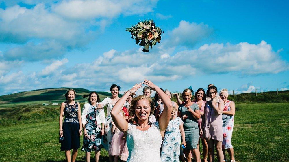 bride throwing wedding bouquet flowers