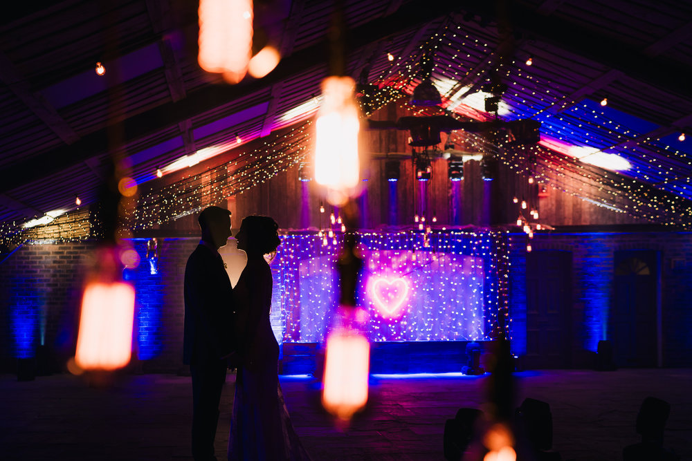 silhouette of bride and groom shot through lights by luminate events at cheshire wedding venue