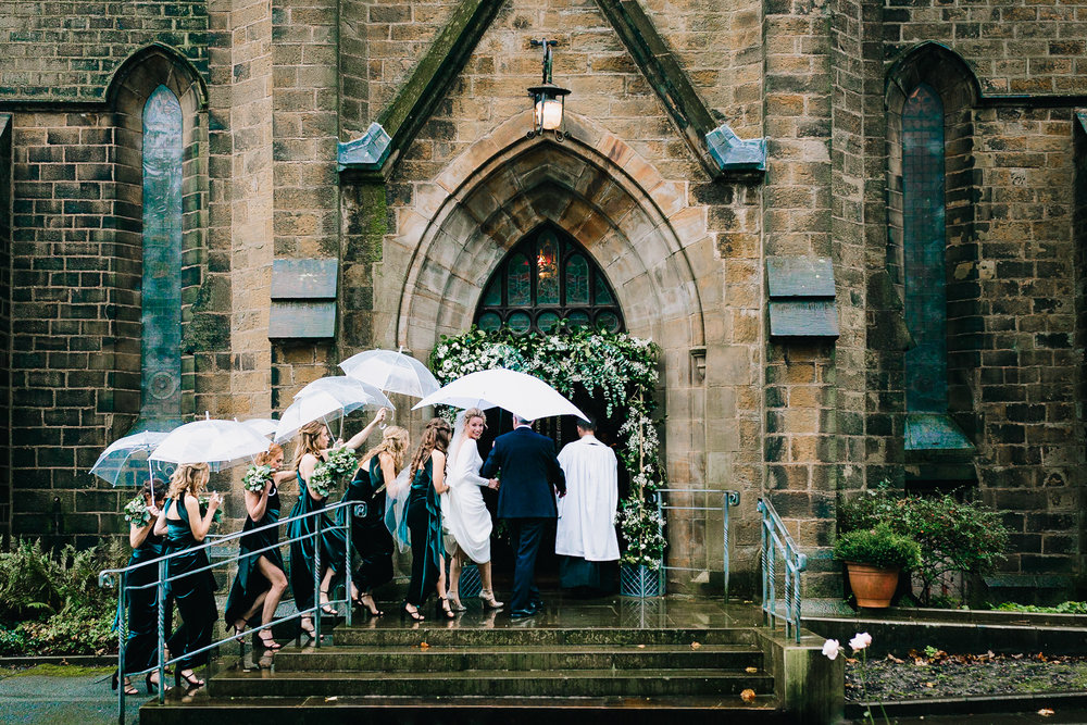 BRIFDE AND BRIDESMAIDS GOING INTO STAFFORDSHIRE CHURCH IN THE RAIN WITH UMBRELLAS