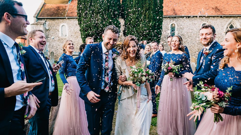BRIDE AND GROOM WALKING THROUGH CONFETTI AT LONDON WEDDING