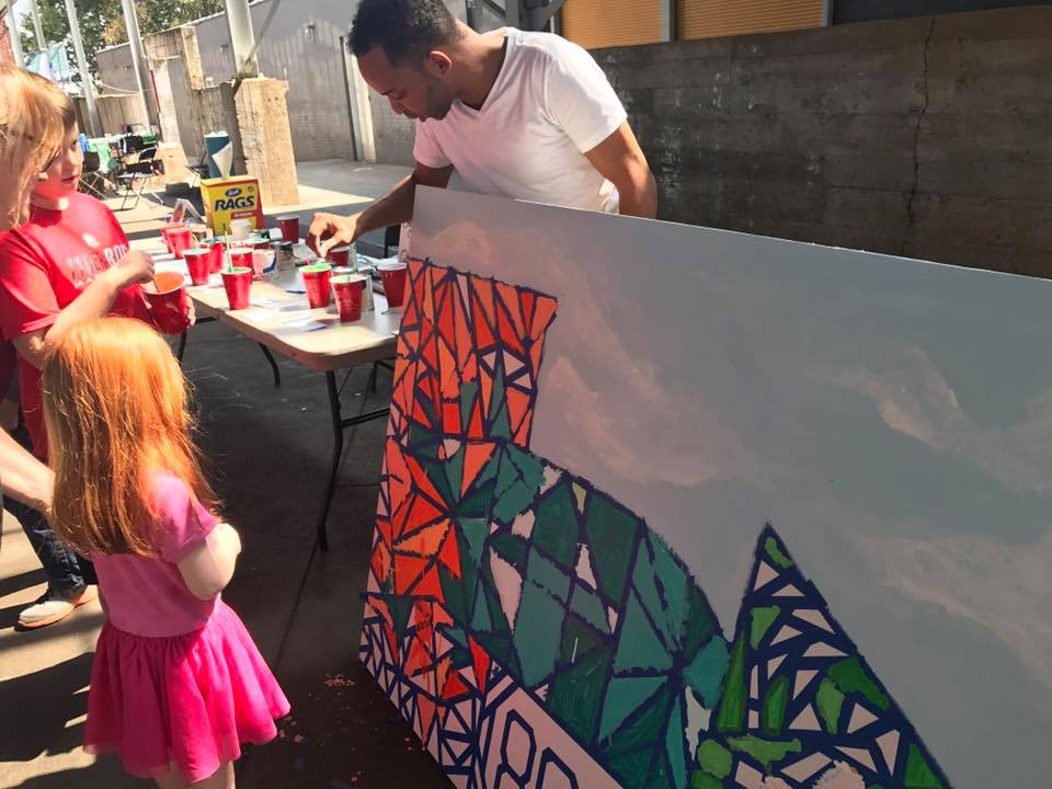 "Josiah guides young participants to painting on the ""Color Your City"" mural at the Mini Maker Faire. Photo by Olga de Klein."