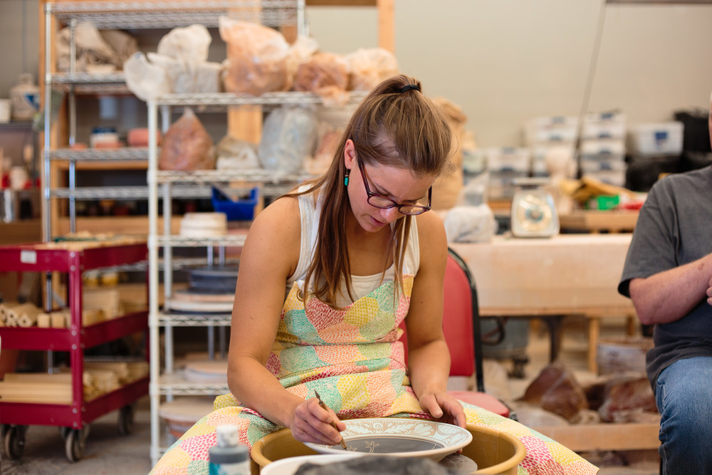Potter working at pottery wheel studio interior