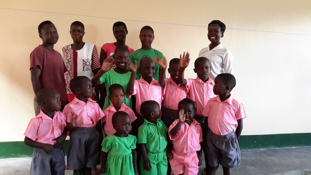 Acorn grads with their children modeling uniforms they were contracted to sew for a local school.