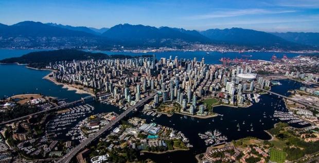 Vista area del centro de Vancouver. Abajo a la izquierda se puede ver la isla de Granville donde existen mercados y restaurantes. Al fondo se puede ver la ciudad de West Vancouver y las montañas con la pista de ski de Cypress. A la izquierda del centro de Vancouver (Donde estan los rascacielos) se encuentra Stanley Park. Uno de los parques urbanos mas grandes de norte América.