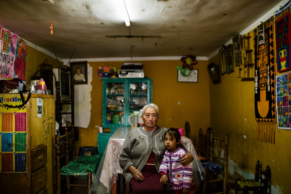 Nicolasa Tolentina Palacios Gamarra (64 years old) and her granddaughter. She shares her small house 20 meters away from river Qillqay with seven relatives. She'd love to move to a more secure part of the city but cannot afford it as prices went up very quickly during the last twenty years.  The lack of a real warning system is problematic: every time the water level gets higher, some rumors and fake alarms start spreading, creating panics in the neighboorhood. Nicolasa sees it with a fatalistic eye:  «when your time has come, your time has come».