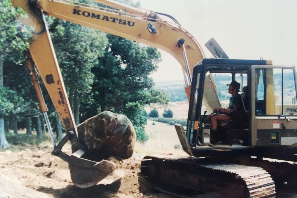 Digger placing rocks to form contouring