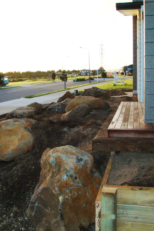 Large rocks and railway sleeper edge around deck