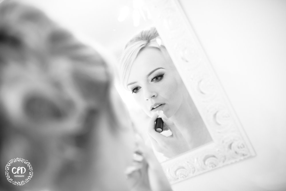 Bride applying lipstick in a mirror