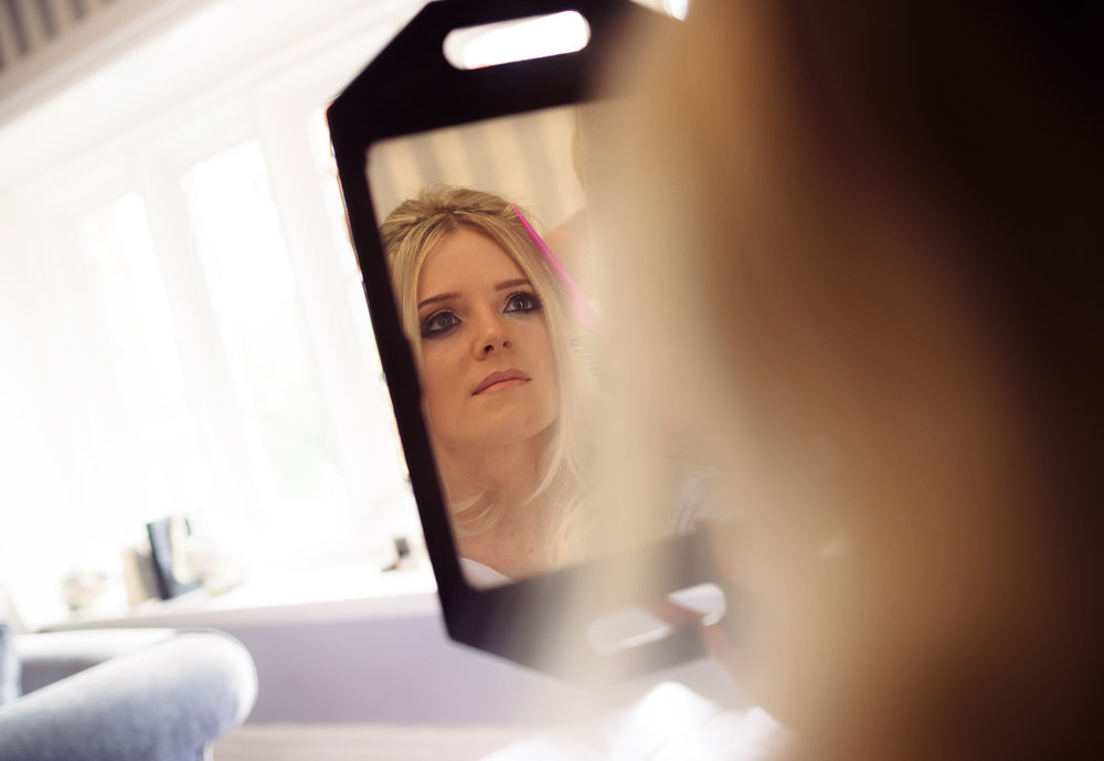 Bride looking into a mirror during makeup