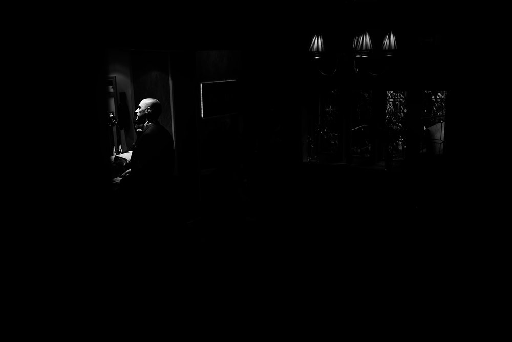 Black and white image of a guy patiently waiting at the bar