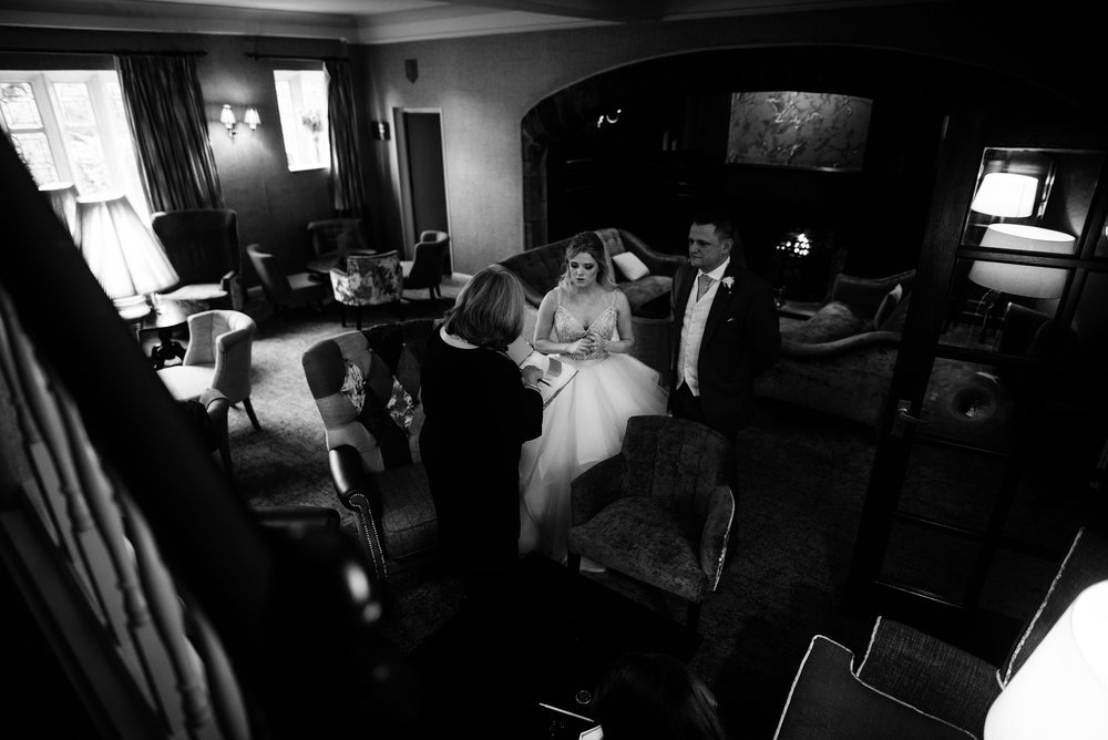 Black and white image of a very nervous bride talking to the registrar