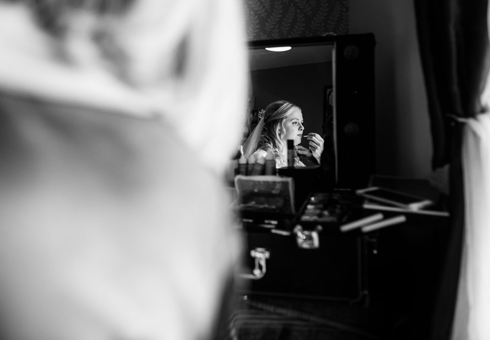 Bridal portrait though a mirror during morning preparations