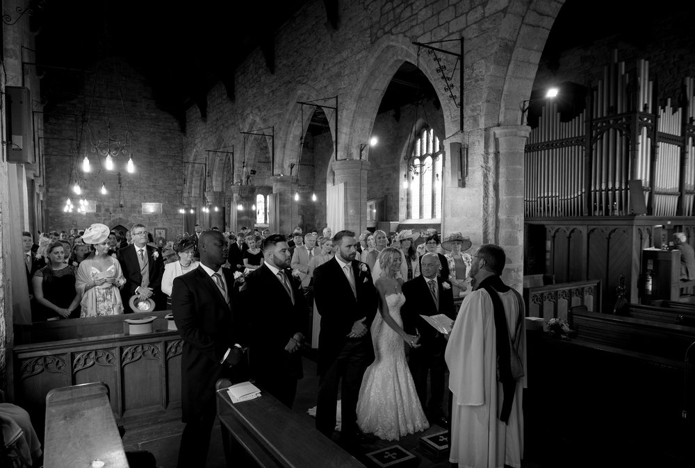 A black and white image of the bridal party in the church