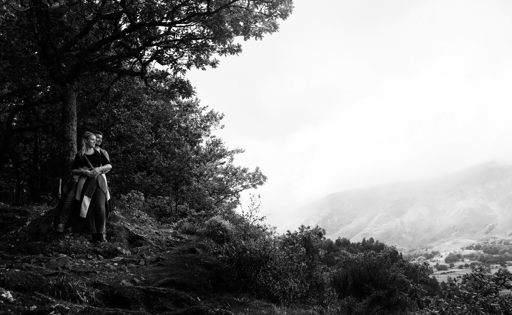 Wide image in black and white of Laura and Johnny looking over the lake with the Borrowdale valley in the background