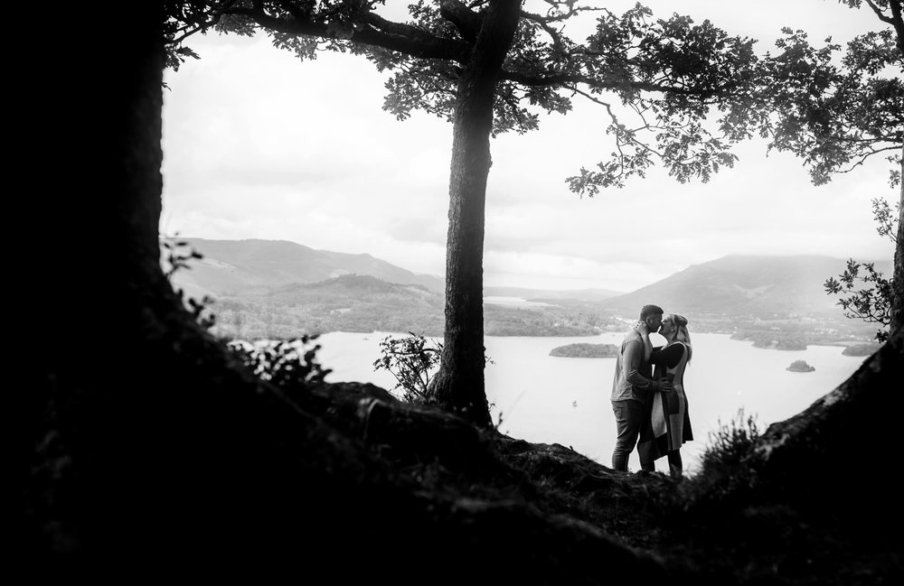 Black and white image of the couple almost kissing with Derentwater in the background