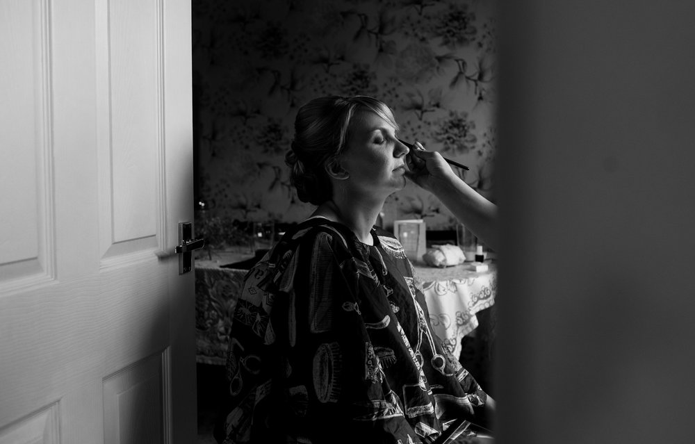 Black and white image of the bride having her makeup applied during morning preparations