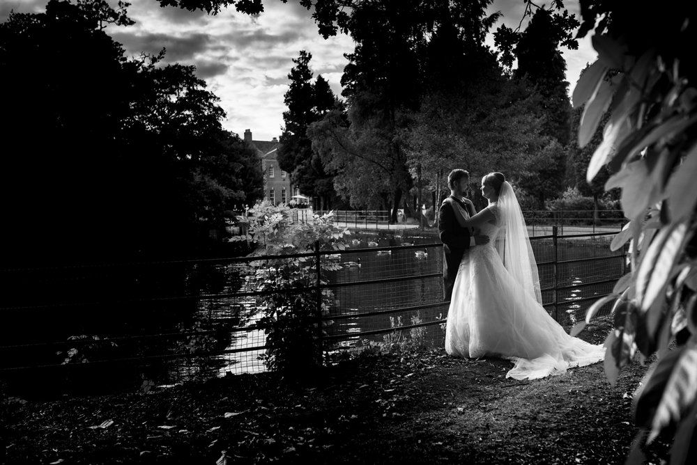 Black and white portrait of the bride and groom with the lake and hall in the background the swans even came over to say hi