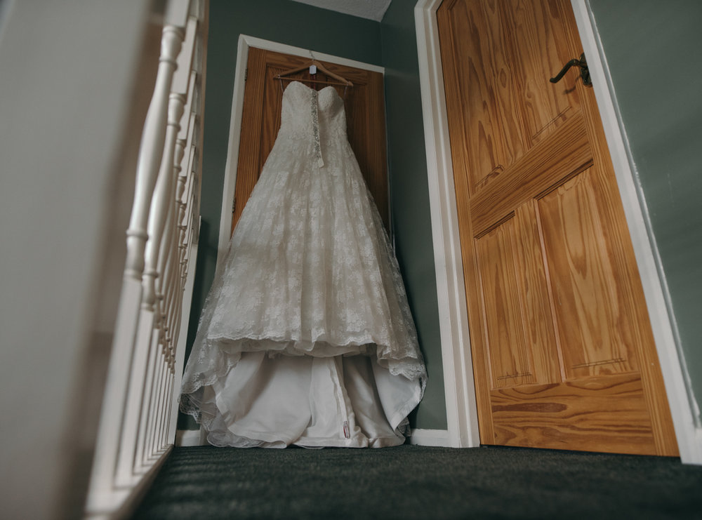 Brides dress hanging in the hallway